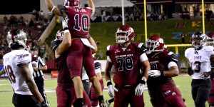 The NMSU Aggies celebrate a third-quarter touchdown in Saturday's game against the Troy Trojans at Aggie Memorial Stadium. The 46-yard Tyler Rogers TD pass to receiver Izaiah Lottie made the score 20-9. The Aggies would pull to within three, but eventually lost 27-24. (Photo by Chase Cordova/Kokopelli)