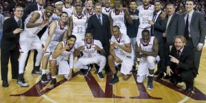 The NMSU men's basketball team and coaching staff celebrate a win over UMKC at the Pan American Center Feb. 24. (Photo courtesy of Gary Mook)