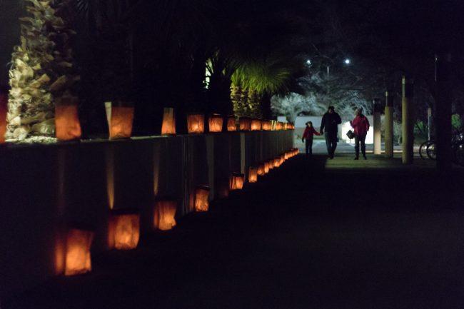 A family strolls the luminaria-filled NMSU campus during the 34th annual Noche de Luminaries event, Sunday Dec. 2, 2018. (Photo by Garrett Tucker/Kokopelli)