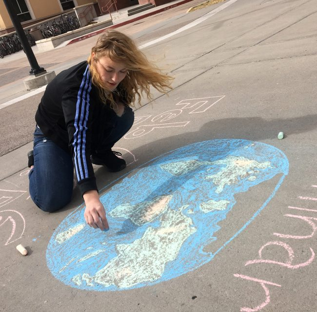 NMSU student Autumn Pearson, a junior majoring in environmental science, creates a chalk drawing on Frenger Mall to help promote Wednesday's Climate Change Education Seminar Series lecture by Katharine Hayhoe, one of the world's preeminent climate scientists. The presentation will take place Wednesday, Feb. 6, at 6:30 p.m. inside Domenici Hall. (Kokopelli photo)