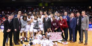 The men's team celebrates in the Pan Am Center earlier this month after winning the WAC regular-season title. The men finished 15-1 in conference play. (Photo by Chase Cordova courtesy of NMSU Athletics)